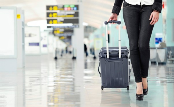 young-woman-airport-pulling-luggage-hand-baggage
